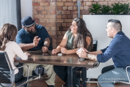 Four people of mixed races and sexes around the table discussing a start-up idea in business meeting